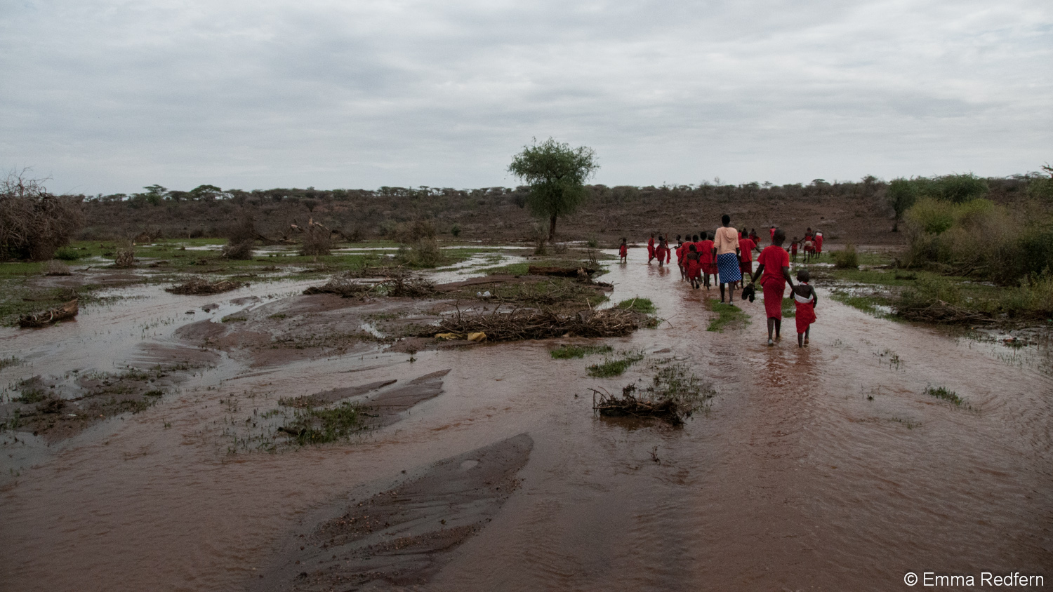 School children walking across flooded land - Isiolo County